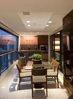 Integrada à sala de jantar, a varanda gourmet tem móveis de fibra sintética que unem conforto e beleza. Com iluminação diferenciada, as pastilhas vermelhas do painel da churrasqueira dão um contraponto interessante ao espaço. Projetada pela designer de interiores Iara Santos.