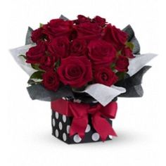 "Lush red roses in a sophisticated polka-dot gift box all tied up with a brilliant red ribbon. Innovative, imaginative, impressive - puttin' on the ritz with a touch of glitz! The ravishing bouquet includes red roses and red spray roses accented with fresh greenery. Delivered in a stunning polka-dot gift box with black and white water-resistant tissue paper set off with a bright red ribbon. Approximately 14"" W x 12"" H"