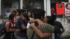 Residents embrace to celebrate that Rev. Jose Luis Sanchez Ruiz has been found alive, at a his church in Catemaco, Veracruz state, Mexico, Sunday, Nov. 13, 2016