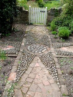 This lovely old tiled and pebbled path makes a pleasing feature in this cottage garden.