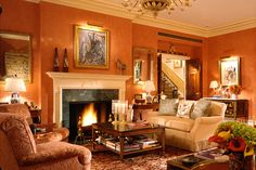 Ellie Cullman's New York City living room, designed in 2005, had Venetian stucco walls painted a rich terra-cotta color that was overwashed in gold to complement her art and antiques. The Venetian chandelier was from Bernd Goeckler Antiques, the obelisks were from Karl Kemp, and the commode was purchased from Guy Regal Ltd., now Newel.