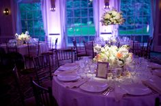 Low floral centerpieces with spotlighting for a wedding at The New York Botanical Gardens. Designed by @xquisiteflowers