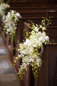 Clusters of white dendrobium orchids tied with satin ribbons adorn the pews of a church.