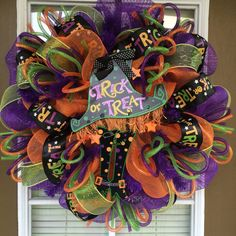 This wreath is made with purple and orange mesh, lime mesh ribbon, trick or treat printed ribbon, deco tubing and a Halloween sign in the
