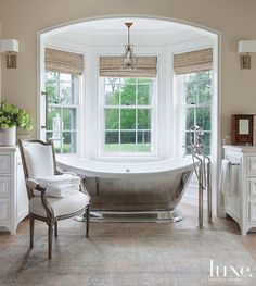A graceful stand-alone #tub affords views of this #Houston home's #backyard