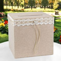 """Natural burlap wedding gift card box is wrapped with lace, jute cording and silver-tone heart charm. Slotted lid opens for retrieving cards. 10"""" x 10"""" x 10""""."""