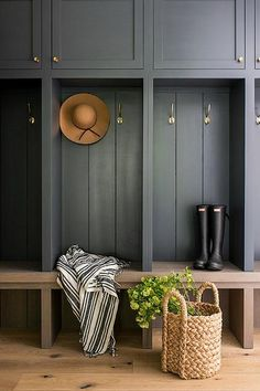 Black shaker cabinets accented with brass knobs are fitted over brass coat hooks mounted against a black plank trim and over a brown oak bench.