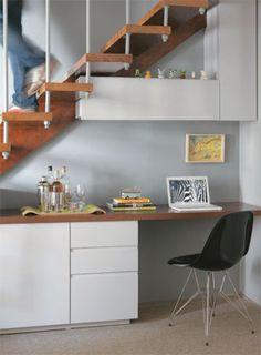 Até a área embaixo da escada, de 2,28 m de comprimento, foi aproveitada: virou home office e bar. Para isso, os arquitetos desenharam o móvel laqueado com bancada, nicho fechado para copos e gavetas para documentos. Os módulos suspensos guardam livros. O móvel sob a escada foi executado pela Móveis Andrade. Cadeira da City Design. No lavabo, a parede recebeu tinta da Suvinil (ref. R-094).
