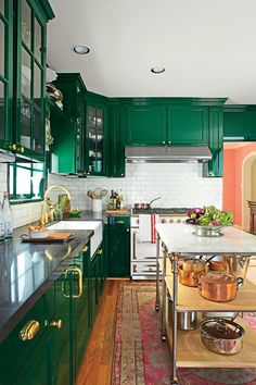 The McCarthys replaced their lower cabinets and gave the uppers new life with glass doors and brass hardware. Tired of white kitchens, they drenched the space in deep, dark green in a glossy, laquered finish. A collection of white dishes, an impressive La Cornue range, and a white subway-tile backsplash bring balance.