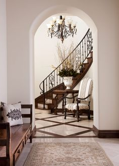 LOVE the floors by the staircase. An imposing side entry features a graceful curved staircase and treillage stone and wood floors. The interior finishes selected integrate and harmonize with the architectural backgrounds. Beautiful Interiors, Beautiful Homes, Foyer Flooring, Stone Flooring, Bench Decor, Curved Staircase, Rug, Entry Foyer, Cool House Designs