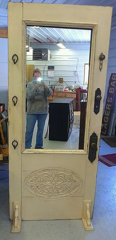 Mirror made from old door. Notice: corbels used for floor stands. Good idea for a free standing piece.