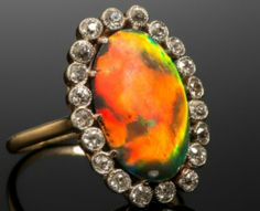 A Lightning Ridge solid black opal and diamond cluster ring, the black opal cabochon weighs approximately 5.00cts and is set within a surround of circular-cut diamonds in platinum and gold.#opalsaustralia