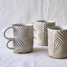 handmade mug of a light toasty colored stoneware glazed with a creamy satin white glaze with a hand carved diamond design. due to the handmade nature of these mugs each is unique and one of a kind.
