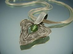 Angel Wings - This pendant is made of fine silver from PMC (precious metal clay). The shape reminds me of angel wings which is a comforting thought. I formed and carved it by hand, then fired and finished the surface. It has been heavily oxidized, buffed out and burnished so that there are different textures that catch the light. The green Swarovski crystal in the middle is subject to change.