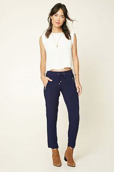 A pair of woven pants featuring a wide-leg design, self-tie drawstring waist, and two front zipper pockets.