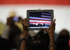 A woman photographs a public event using her iPad. Photo by Phil McCarten of Reuters.