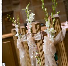 The couple decorated the pews with champagne ribbons and pink dendrobium orchids.