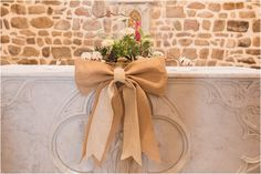 Neutral hessian bows on the wedding alter | Image by Sophie Reynaud