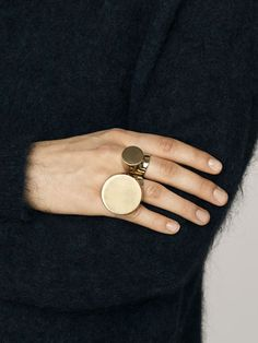 """Create a bold statement with By Malene Birger's statement ring, crafted from gleaming metal. This futuristic style features a signet-style disc with a brushed finish in a play on textures. Team it with the corresponding Madge ring and a glossy manicure for a strong and modern look."""