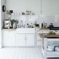 white tiles, farmhouse sink, butcher block countertops, painted white wooden floor