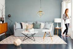 peinture murale bleu-gris, canapé gris clair, chaise design blanche et table basse en marbre blanc dans le salon