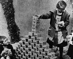 German children playing with stacks of hyperinflated currency during the Weimar Republic 1920s. At its worst in Nov 1923 $1 US = 4.2 Trillion German Marks. So much money was needed people had to carry it about in wheel Barrows.