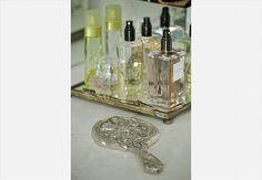 Para agrupar todos os perfumes em um único espaço, sobre a bancada do banheiro, as arquitetas Andrea Reis e Adriana Khalifeh utilizaram uma bandeja antiga