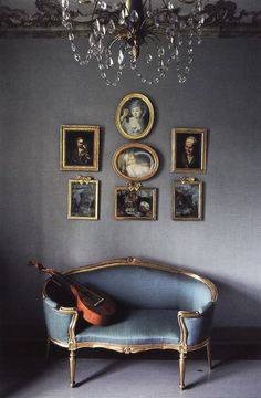 grey walls brining art with gold frames above an antique sofa to life