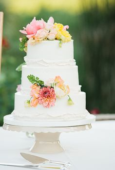 A three-tiered white wedding cake decorated with ruffled fondant details and fresh flowers, created by Cake Cathedral.