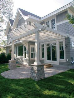 Traditional structures like this new pergola–porch can be built from modern materials that are impervious to moisture and insects (Kleer Lumber components from Tapco).