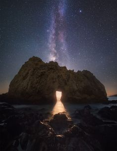 Milky Way Moonset.  The Milky Way is almost exactly vertical, plunging down into the Pfeiffer Beach Keyhole Rock, a natural arch carved by erosion. But what's that glow in the hole? That's the crescent Moon, setting into the horizon but blocked by the rock itself. The Moon's path across the sky against the background stars passes fairly close to the center of our spiral galaxy, which we see edge-on because we're inside it.