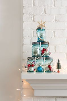This idea's perfect for a mantel or entry table: Fill six like-sized canning jars with ornaments, tinsel, greenery, you name it. Assemble the jars in a pyramid, then wrap it with a shiny garland and top with a star. Done!   - CountryLiving.com