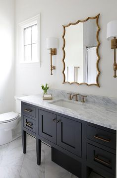 Antique brass French sconces flank a gold leaf vanity mirror hung over a black washstand accented with brass pulls and a white and gray marble countertop finished with a brass faucet.