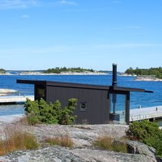 Five blackened timber structures dot the shoreline of a remote island in the Stockholm archipelago to form a holiday home by Margen Wigow Arkitektkontor