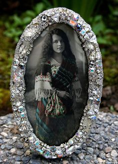 A truly stunning small jeweled frame... A vintage metal oval frame from the 30s has been gifted new life with a collection of vintage rhinestones which have been meticulously hand-set around its rim. A trio of vintage glass leaves have been incorporated into the mix. Sterling silver micro beads sugar the sides and will tarnish over time adding a rich patina against the bling. Frame now holds a cutout of a vintage postcard depicting a lovely gypsy woman. Picture may be removed to hold a…