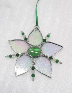 No shoveling required ! This snowflake will stay on your window no matter how warm it is inside. 5 clear ice glass arms with a large green glass center nugget. 5 beaded wires between the arms have green and clear glass beads. 5 1/2 long and 5 1/2 wide The stained glass is hand cut by