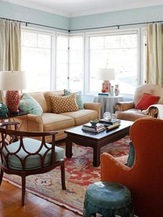 Living Room - The cool blues of this space are quickly warmed up by the bright reds. The corner window enlarges, the cozy cushions invite, and the unique accents lure you to explore their individuality. I am especially in love with the turquoise metal side table and the blue seat with star-shaped wooden back.
