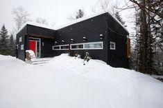 Chopped wood fits into the side of a huge black fireplace at this chalet in Quebec, which provides a winter retreat for a family of skiers. Black Fireplace, Concrete Fireplace, Quebec, Black House, Skiing, House Design, Cabin, Warm, Architecture