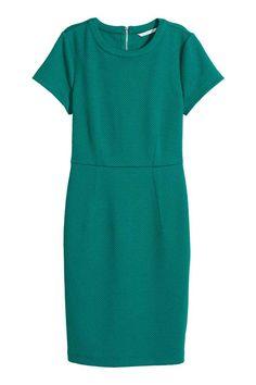 Jurk met structuurdessin: Een nauwsluitende jurk van tricot met een structuurdessin. De jurk heeft korte mouwen, een naad in de taille en een zichtbare ritssluiting op de rug. Ongevoerd.