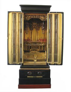 Beautiful antique Japanese butsudan (buddhist shrine for household use), made of lacquered wood in 3 sections, all black lacquer exterior, two sets of gilt lacquer interior doors, inside of shrine ornately carved and lacquered with black, gold and red lacquer; carved with phoenixes in clouds, birds and flowers, and miniature temple architecture; among the interior's many features are: red lacquer railing, columns carved with tiny baku and fu-dogs, many surfaces for offerings,