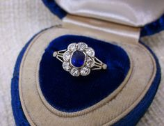 Lovely Edwardian era diamond and sapphire ring. The ring is set with one center 0.36 carat blue sapphire, surrounded by a scalloped halo of 0.50 carats total weigh in Old European cut diamonds, all in platinum topped yellow gold.