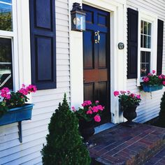 Omg this house is so cute! The black shutters make the white pop and so do the hot pink flowers