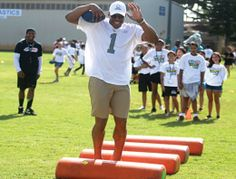 Carolina Panthers quarterback Cam Newton demonstrates how to run a drill at a mini-football camp for NFL Play 60 at Ward Field, Joint Base P...
