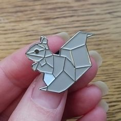 What team are you on? Are you a grey squirrel fan, or a red squirrel fan? Frankly, we love them both equally, so weve immortalised that love in enamel pin form, with a geometric twist.  Hand drawn, and UK made, our squirrel pin comes in two variations: - grey with silver nickel outlines and back, or - red with gold nickel outlines and back  Both feature black rubber clasps.   Height: 24mm Width: 25mm  ~  Pins are sent by Royal Mail first class postage in the UK, and standard international…