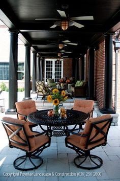 Covered walkway with multiple seating areas and ceiling fans: Poynter Landscape Architecture