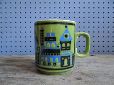 Vintage pottery mug with stylised building pattern in blue & black on a green background. Designed by John Clappison for Hornsea in the 1970s.