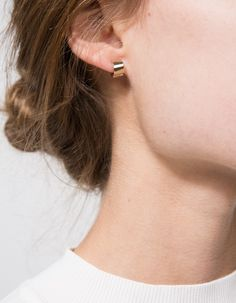 A handcrafted pair of yellow gold small huggie hoop earrings with hinge structure from Loren Stewart with minimalist styling.  •Handcrafted pair of yellow gold huggie hoop earrings •Hinge structure •Straight post •14KT gold •Made in USA