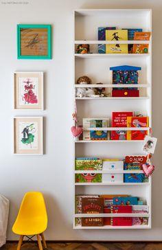 Um estante branca e estreitinha para organizar a coleção de livros e brinquedos.