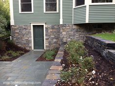 This design turned a somewhat dark and narrow walk-out basement area into a private terraced retreat.  Granite walls and tumbled bluestone patio.