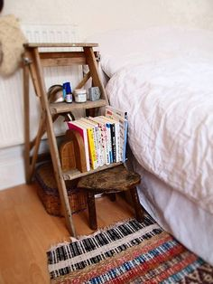 A beat-up old wooden step ladder serves duty as an informal, practical bedside storage piece #clever #DIY